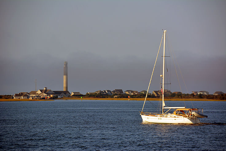 A sailboat in front of Oak Island lighthouse, from Southport NC